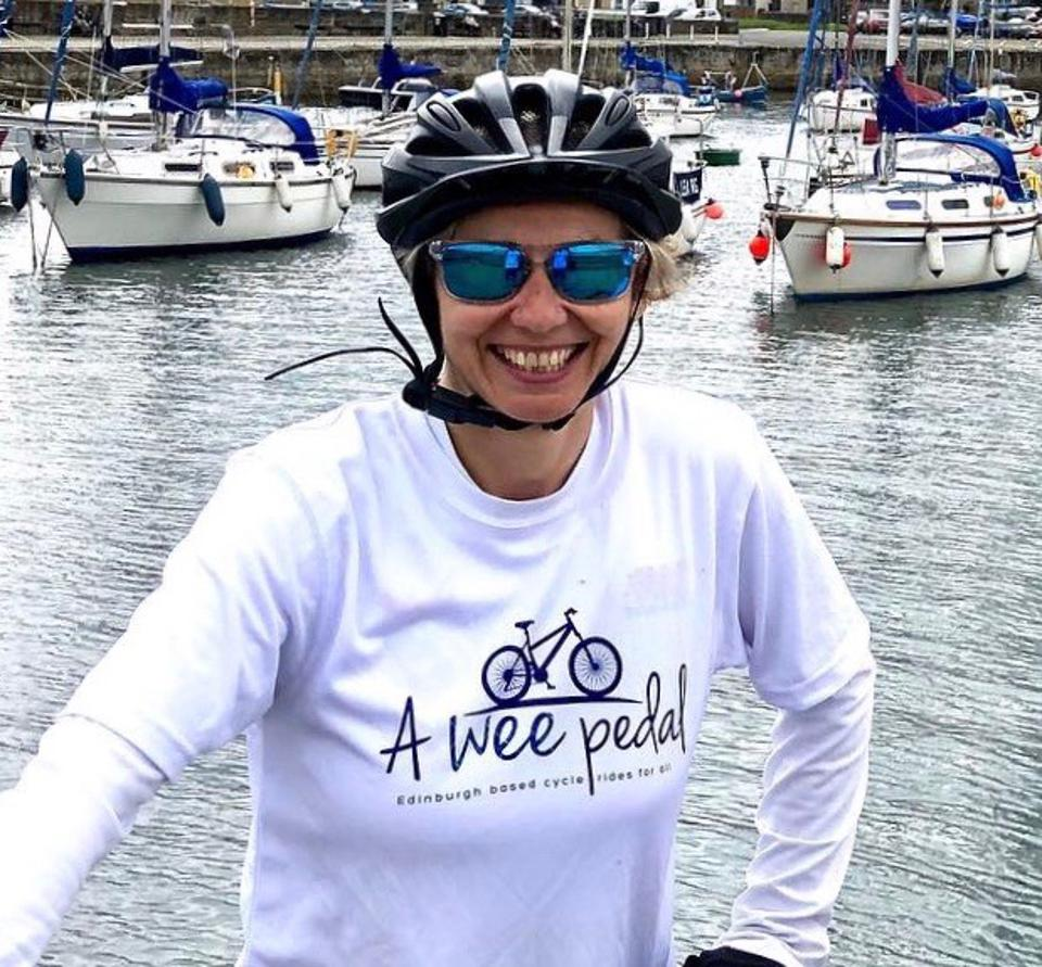 Leanne smiles wearing cycle helmet by a river