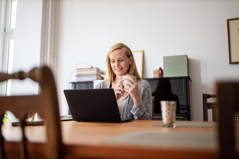 Woman having coffee and using laptop at home