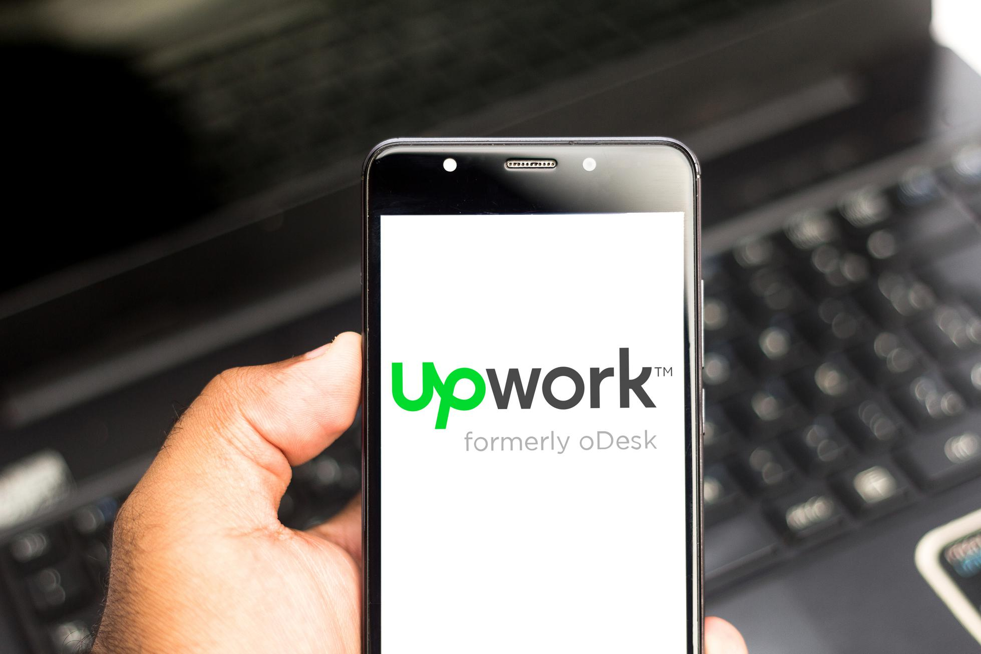 In this photo illustration an Upwork logo seen displayed on...