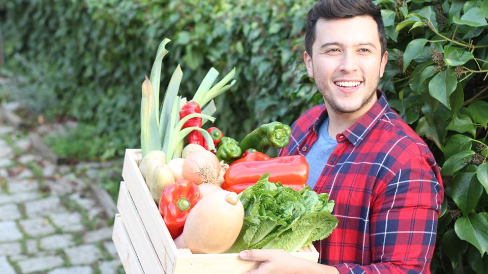 Cute guy holding basket with natural food
