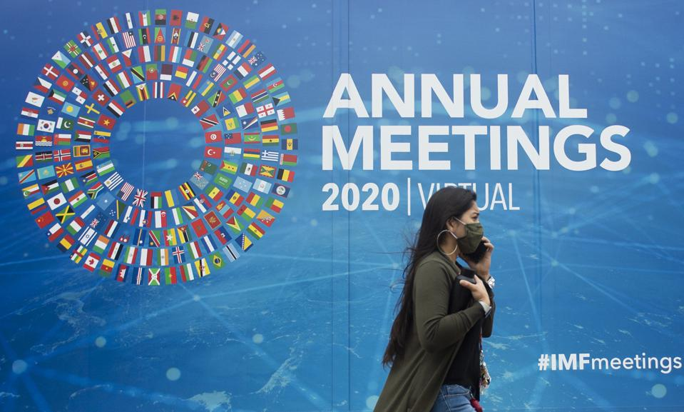 A woman walks past a promotional poster for the virtual 2020 Annual Meetings outside the International Monetary Fund at their headquarters in Washington, DC on October 13, 2020.