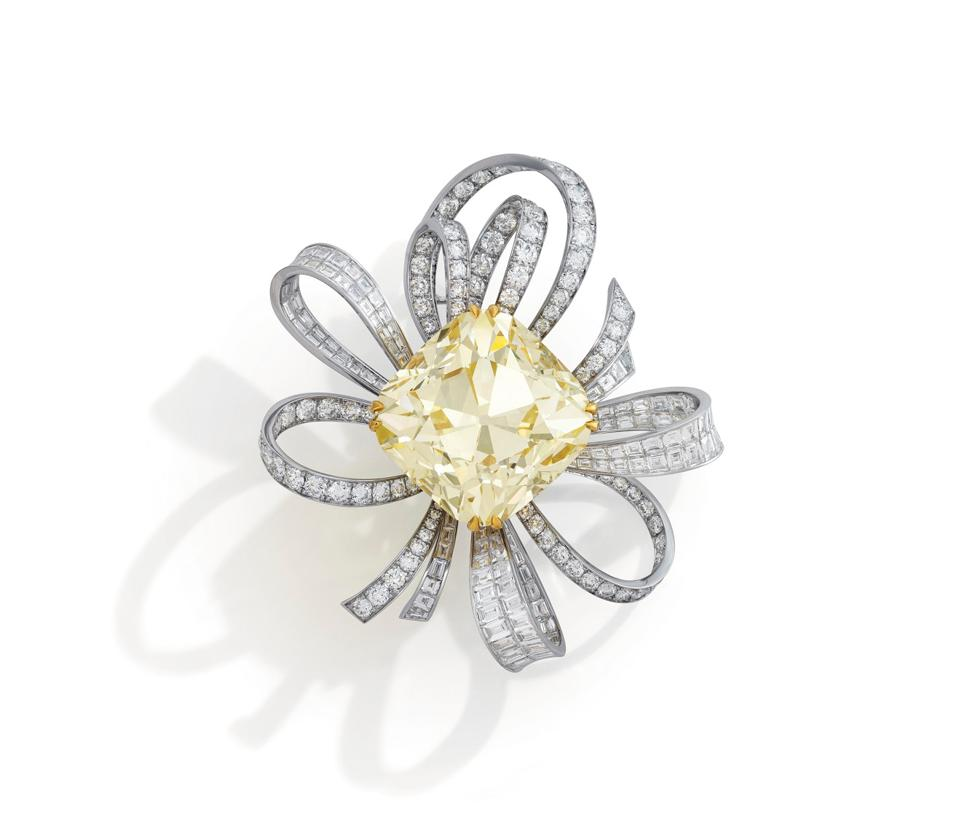A gold and diamond brooch by Graff centered with a 107.46 carat fancy yellow diamond