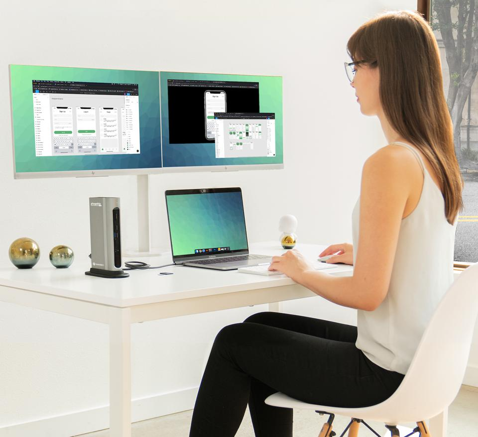 Woman sat at desk with two monitors