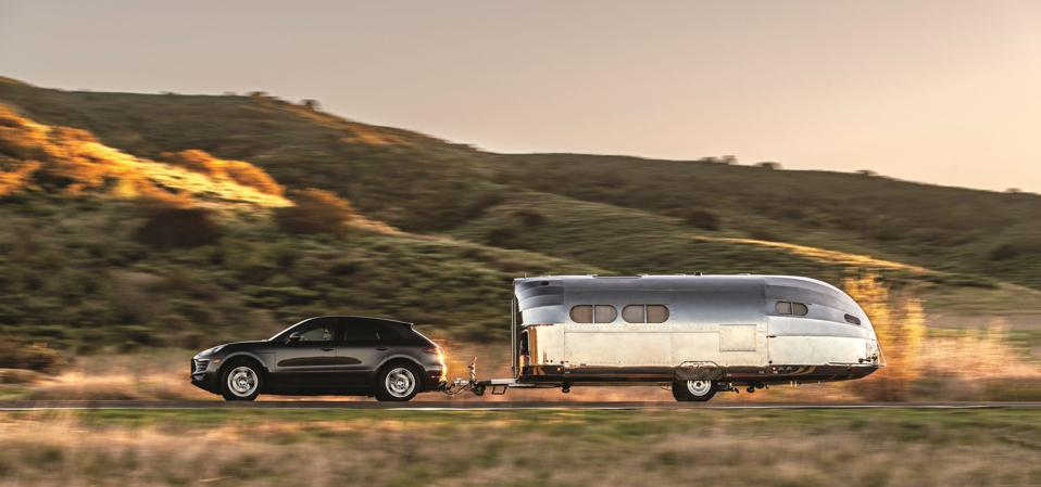 A car towing a streamlined, silver Bowlus recreational trailer.