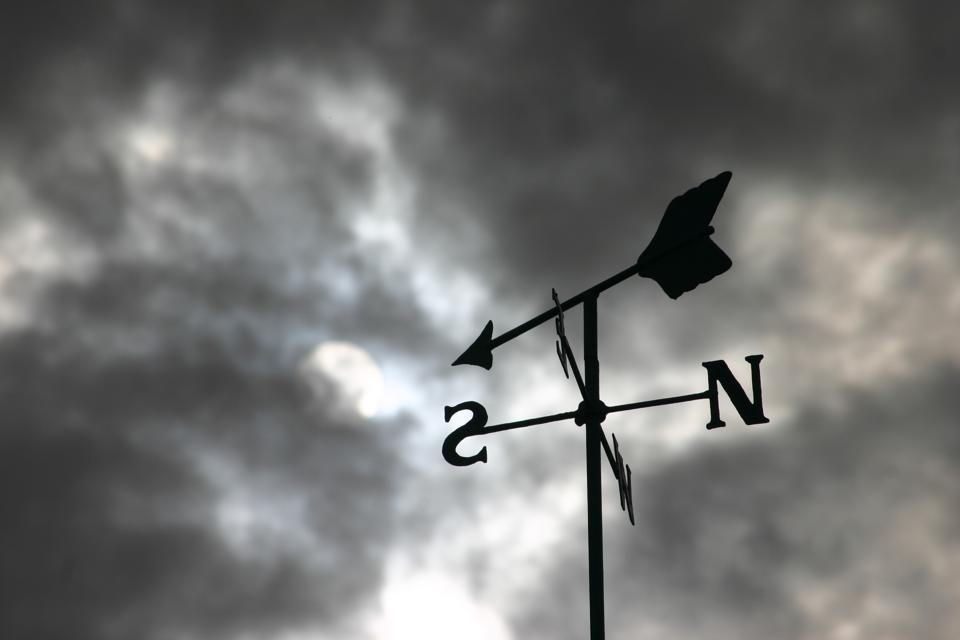 Weathervane and storm clouds showing it can be hard to focus in chaotic times.