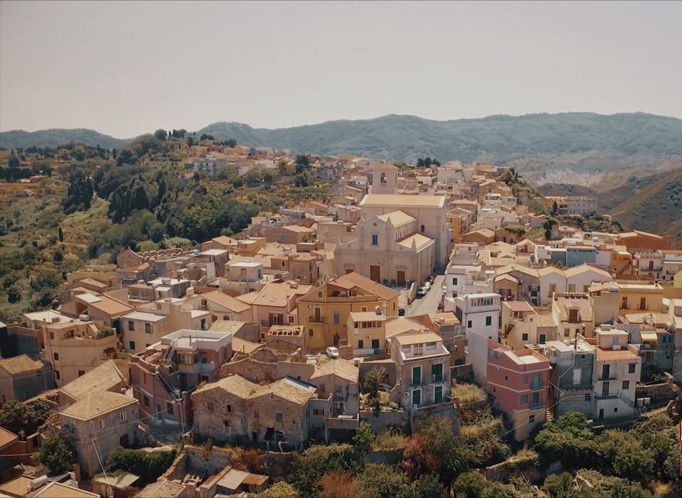 A cluster of brightly colored old farmes dwellings in a pristine green bucolic hilly landscape