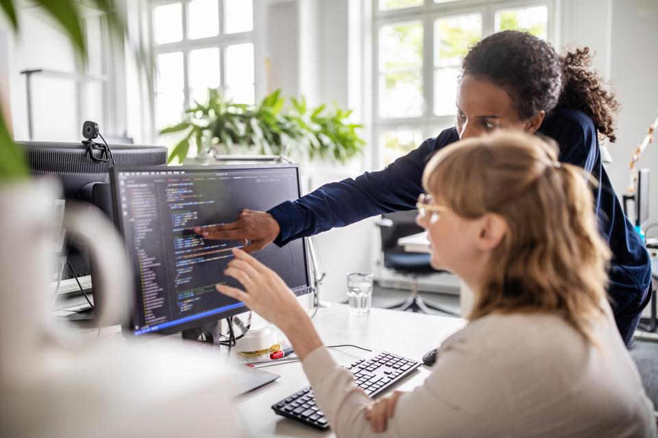 Businesswomen discussing coding on computer
