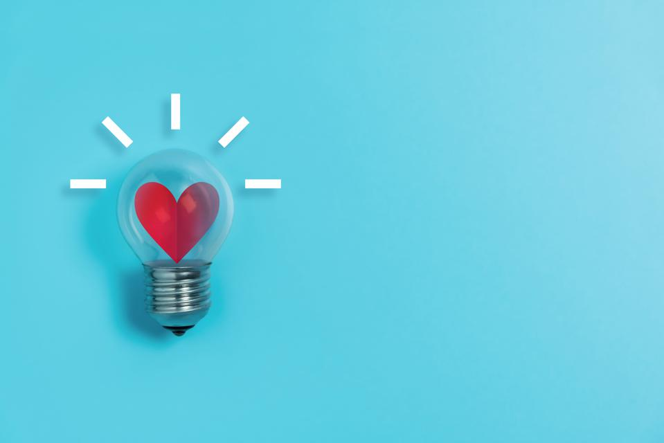 Red heart in light bulb on blue background with copy space.