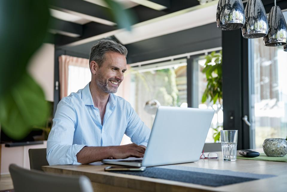Smiling mature man at home using a laptop at table