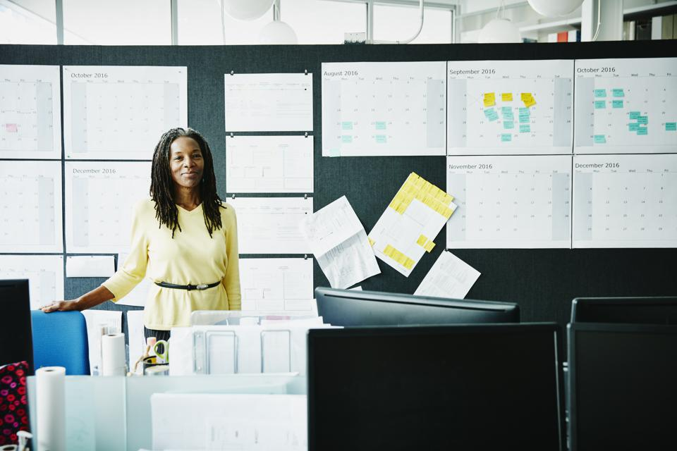 Smiling businesswoman standing at workstation