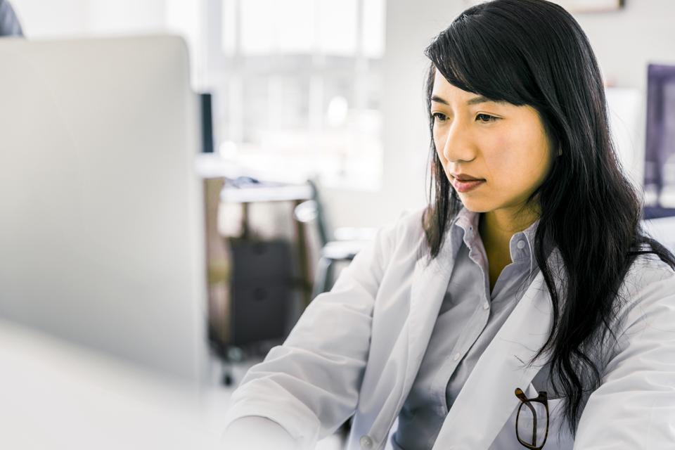 Female doctor using desktop PC