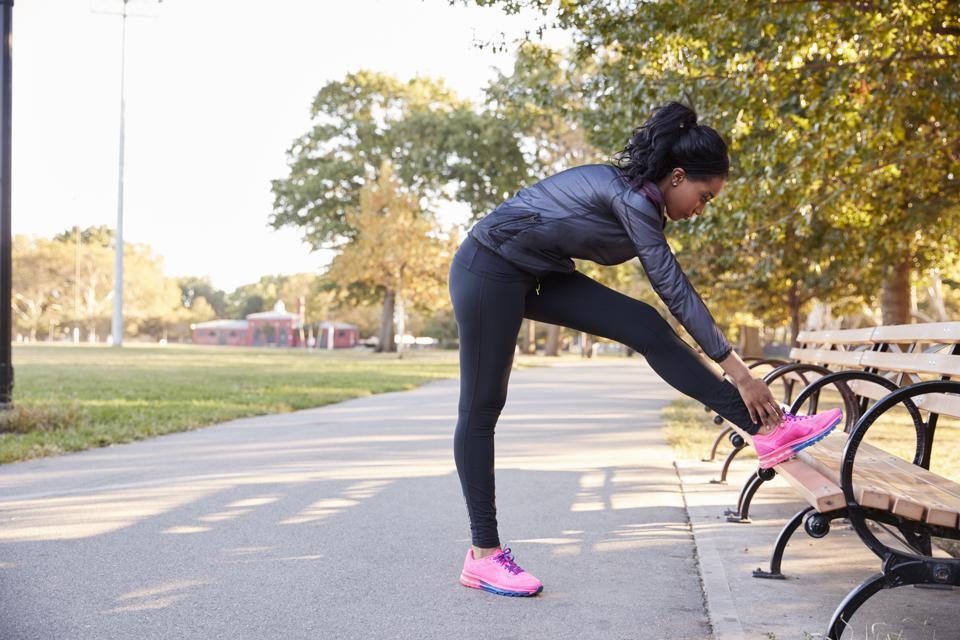Young black woman stretching on bench in a park, full length