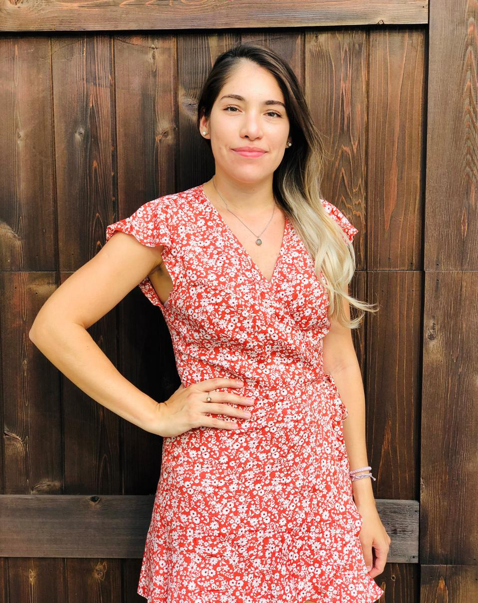 Ilse Calderon is standing in front of a wooden fence, wearing a red and white floral dress. Her right hand is on her hip and she is staring confidently into the camera.