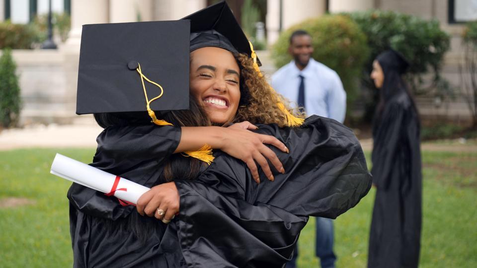 Female graduate hugs friend post ceremony