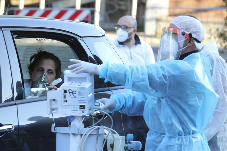Doctors give oxygen to a patient who waits in the car because the emergency room is full in Naples, Italy