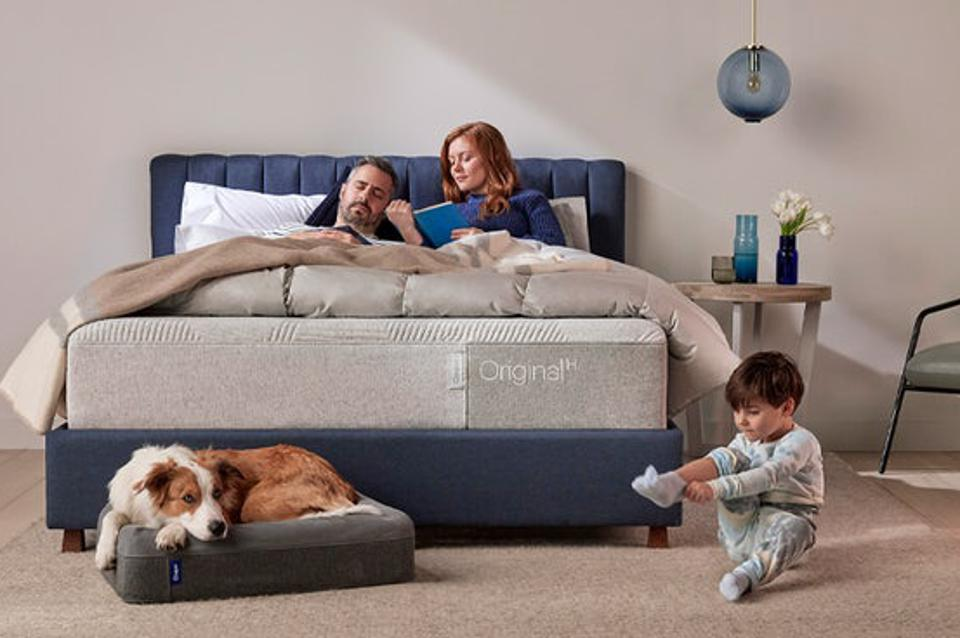 Couple reading on their Casper Mattress with their child and dog at the foot of the bed.