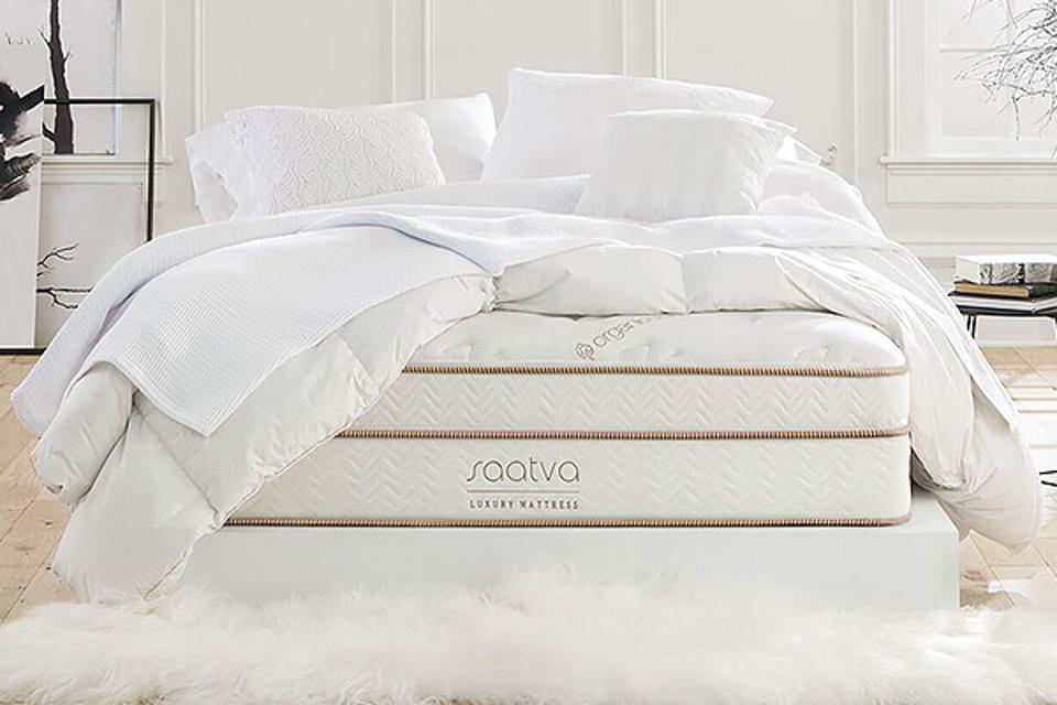 Saatva mattress set up with white bedding on a white rug.
