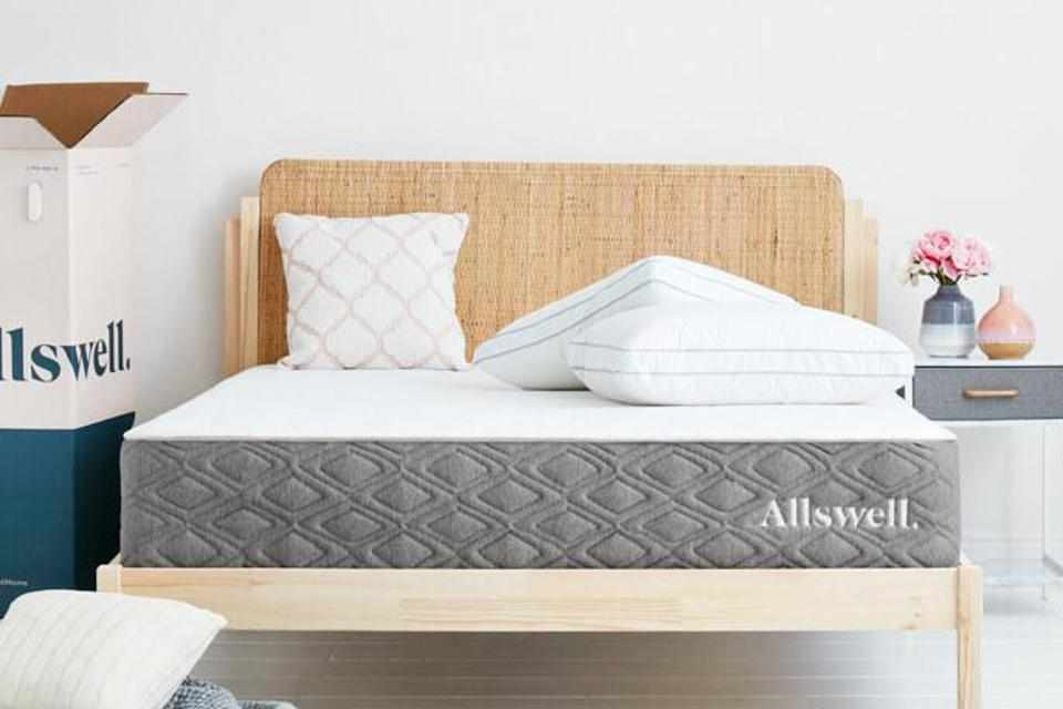 Allswell The Luxe mattress set up on a light wooden bed frame.