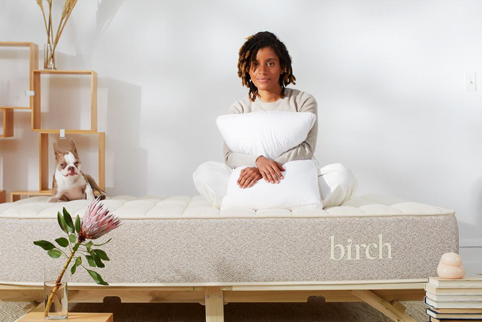 Woman sitting on Birch mattress holding a pillow with her dog next to her.