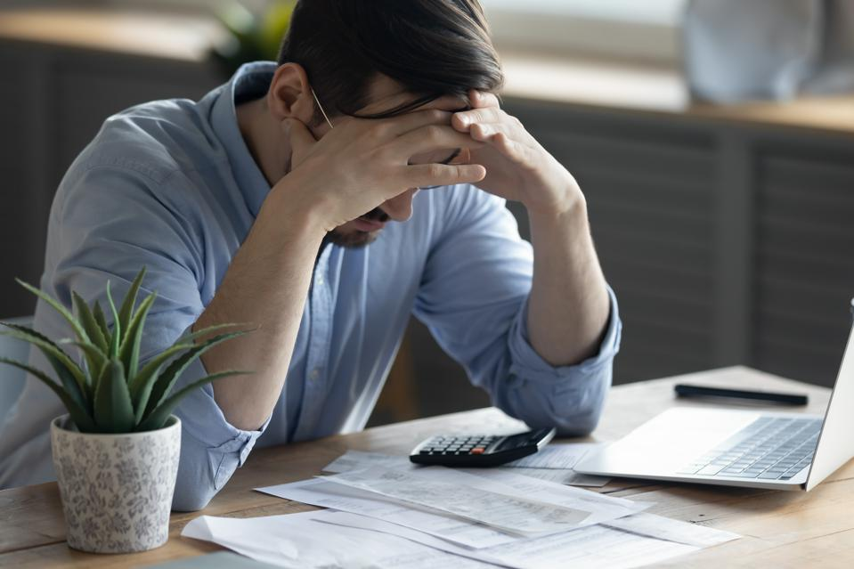 Frustrated man at desk going over cost analysis