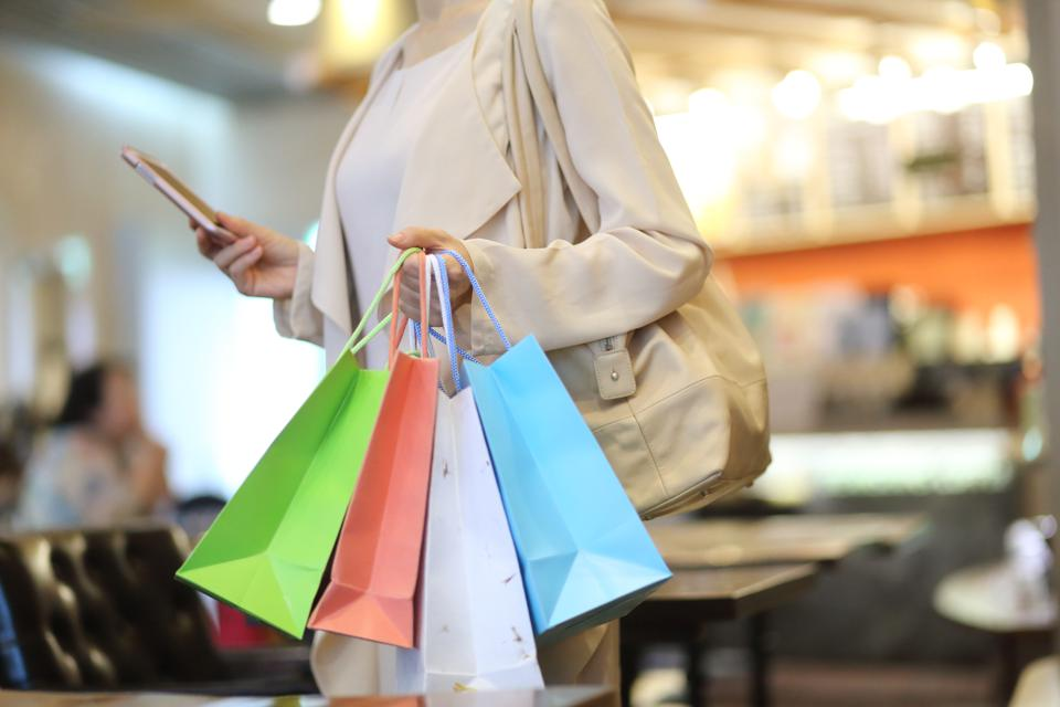 Cropped image of woman with shopping bags using a mobile phone