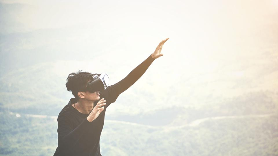 Man Wearing Virtual Reality Simulator On Mountain