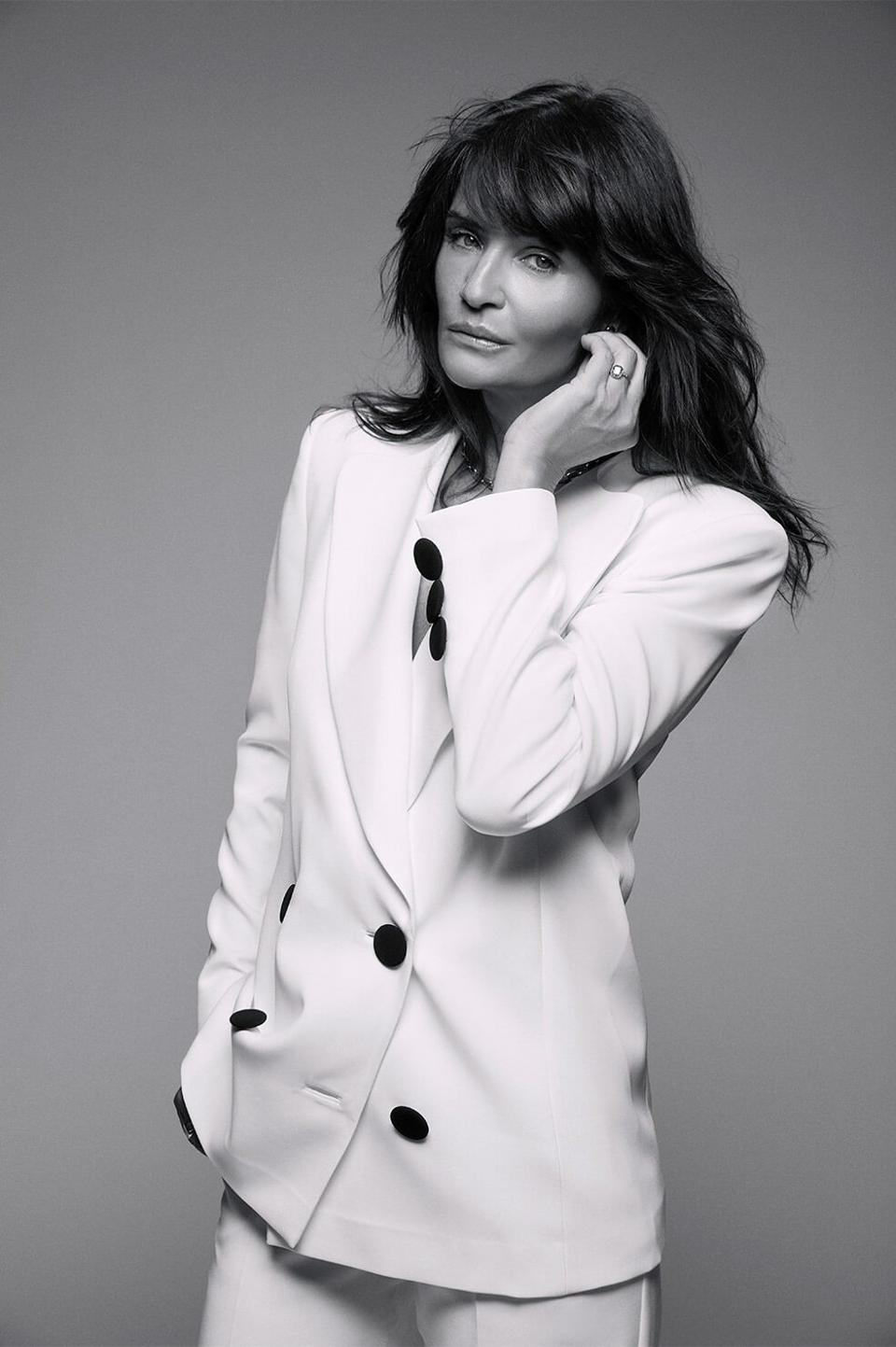 Helena Christensen models a white blazer from her collaboration with Anine Bing.