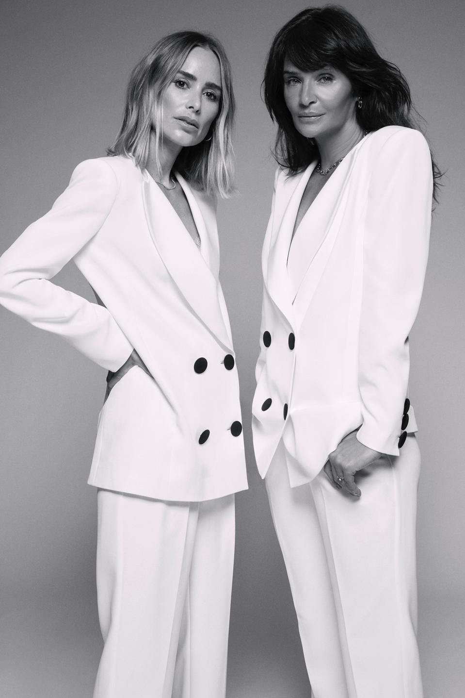 Anine Bing and Helena Christensen model a white suit from their holiday collection.