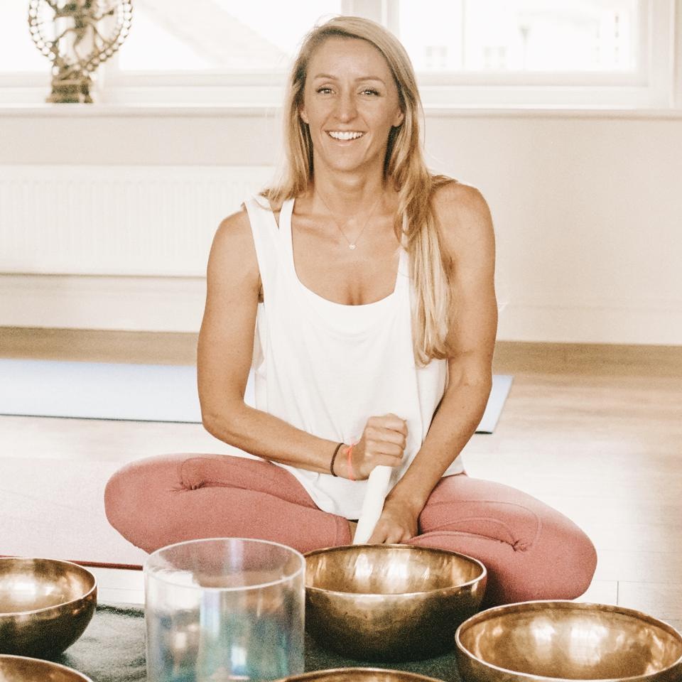 A woman sits on the floor, smiling, with golden bowls in front of her