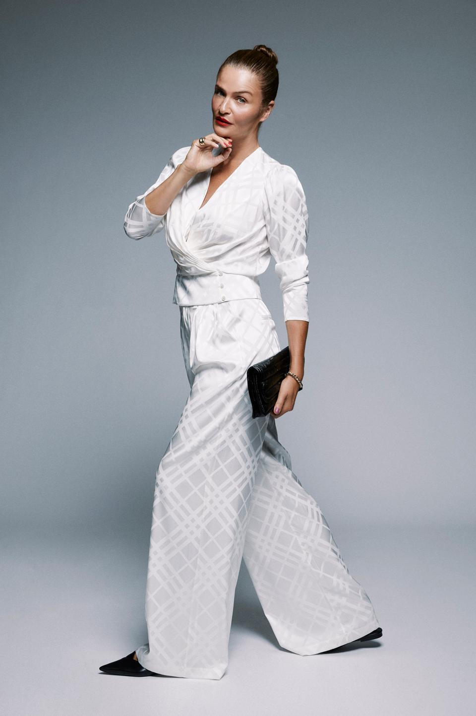 Helena Christensen models a while silk set, part of the model's collaboration with Anine Bing.