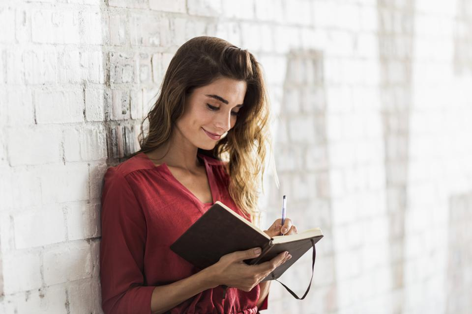 Young female professional taking notes -- thinking about pursuing a dream career?