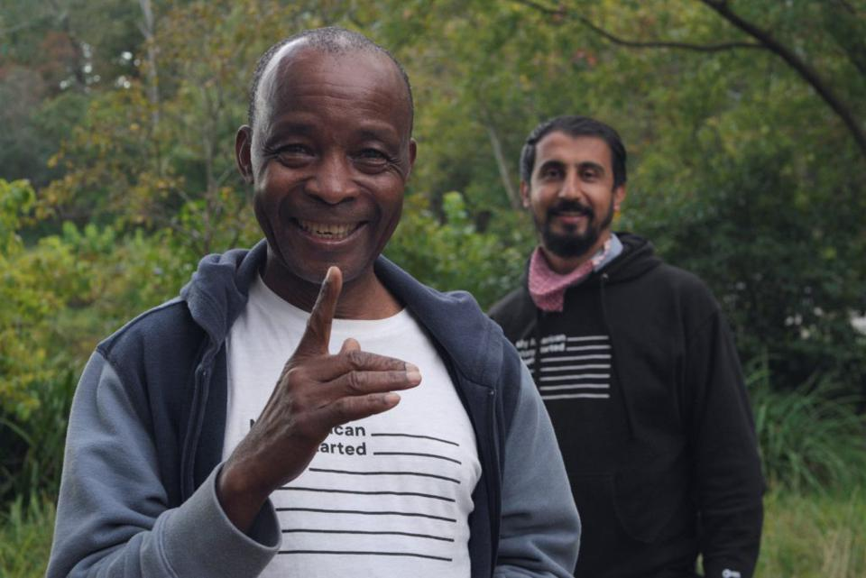 One Black man smiling and one Afghan man in the background with and American flag shirt.