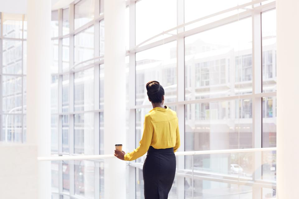Modern business woman looking out the window.