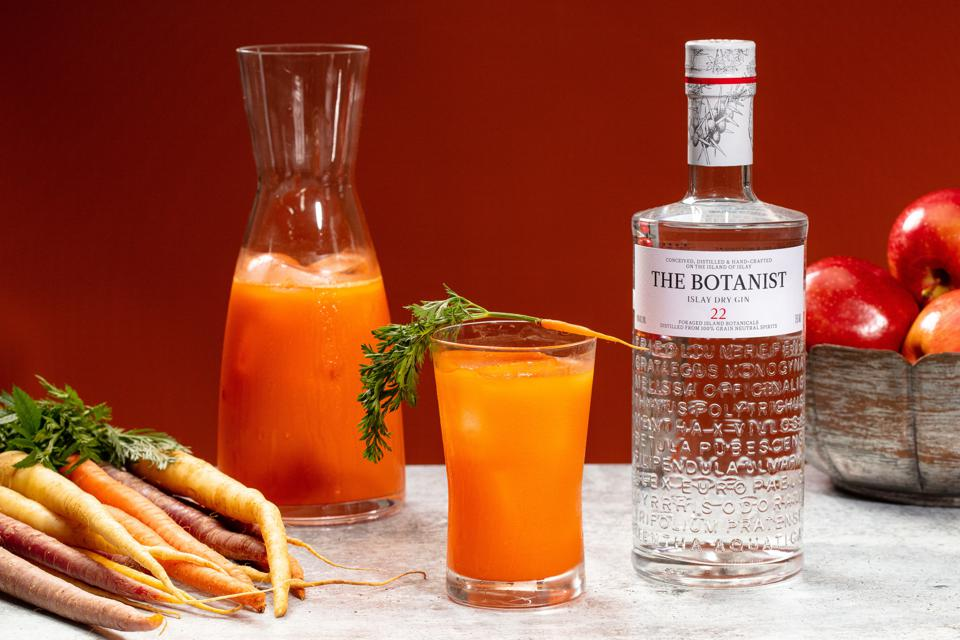 Bottle of The Botanist Islay Dry Gin next to glasses of orange colored cocktails