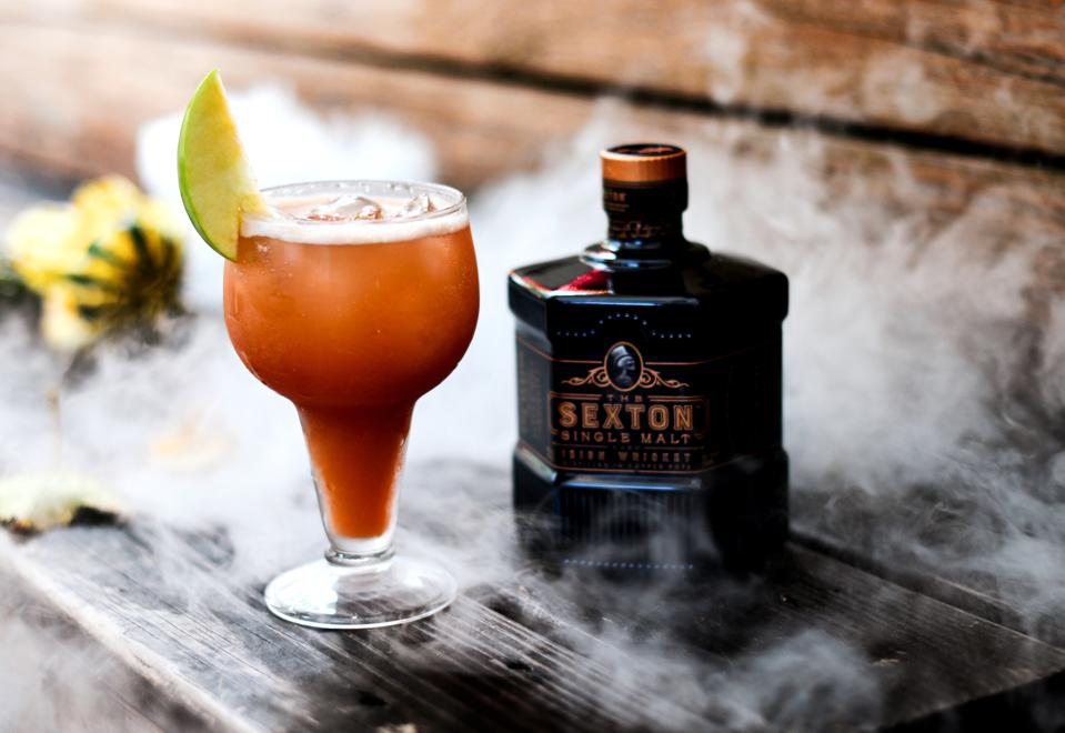 Bottle of The Sexton whiskey and cocktail in a glass.