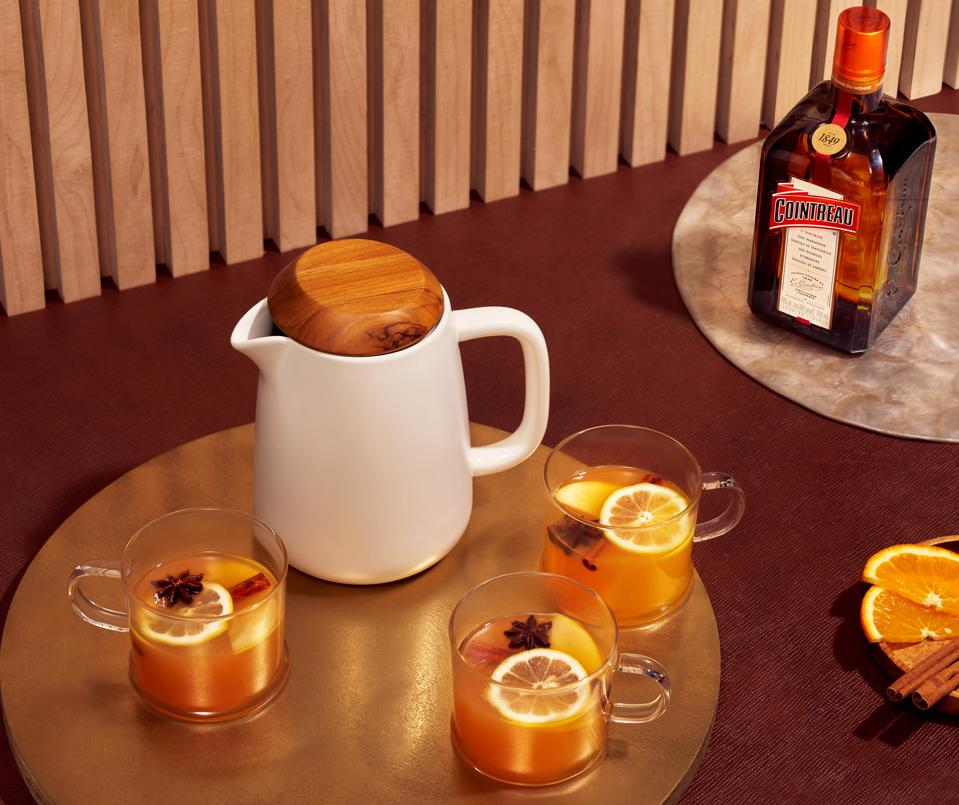 Pitcher of tea, cocktail mugs and bottle of Cointreau