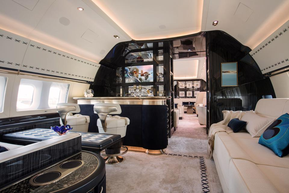 The interior of a private plane with a bar, luxury tables, and more.