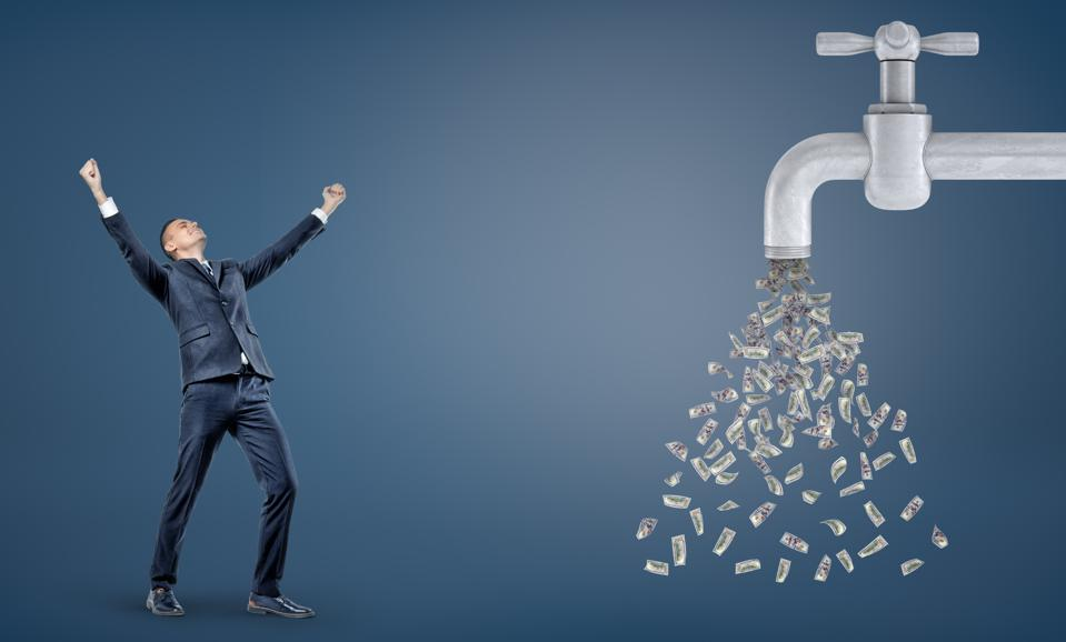 A small victorious businessman stands with raised arms near a giant water faucet leaking a lot of dollar bills
