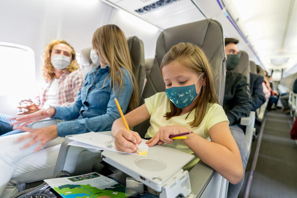 Happy girl traveling and coloring in the plane wearing a facemask