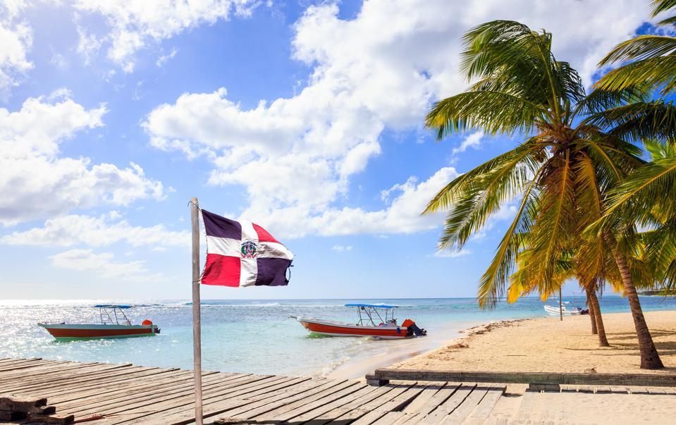 Caribbean beach and Dominican Republic flag beach tropical getaway trip COVID-19