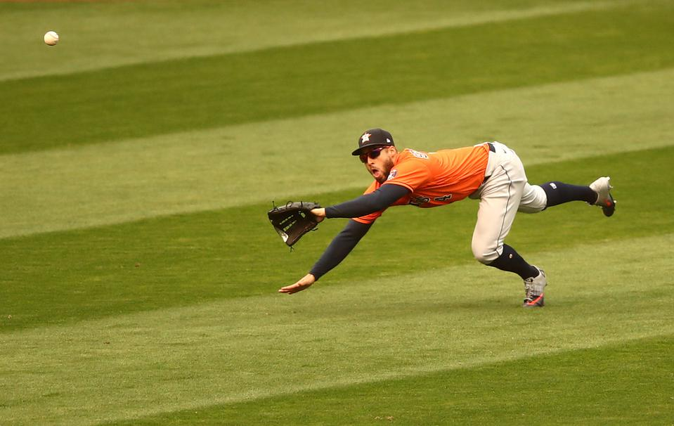 Houston Astros outfielder George Springer is diving to catch a baseball