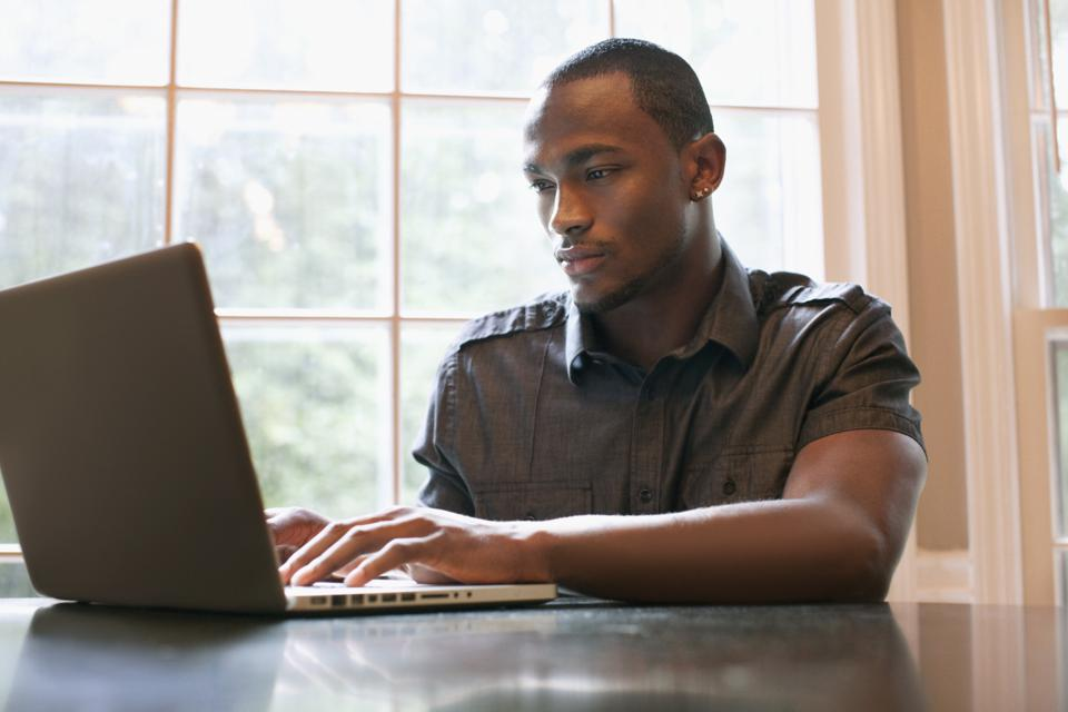 African American man typing on laptop