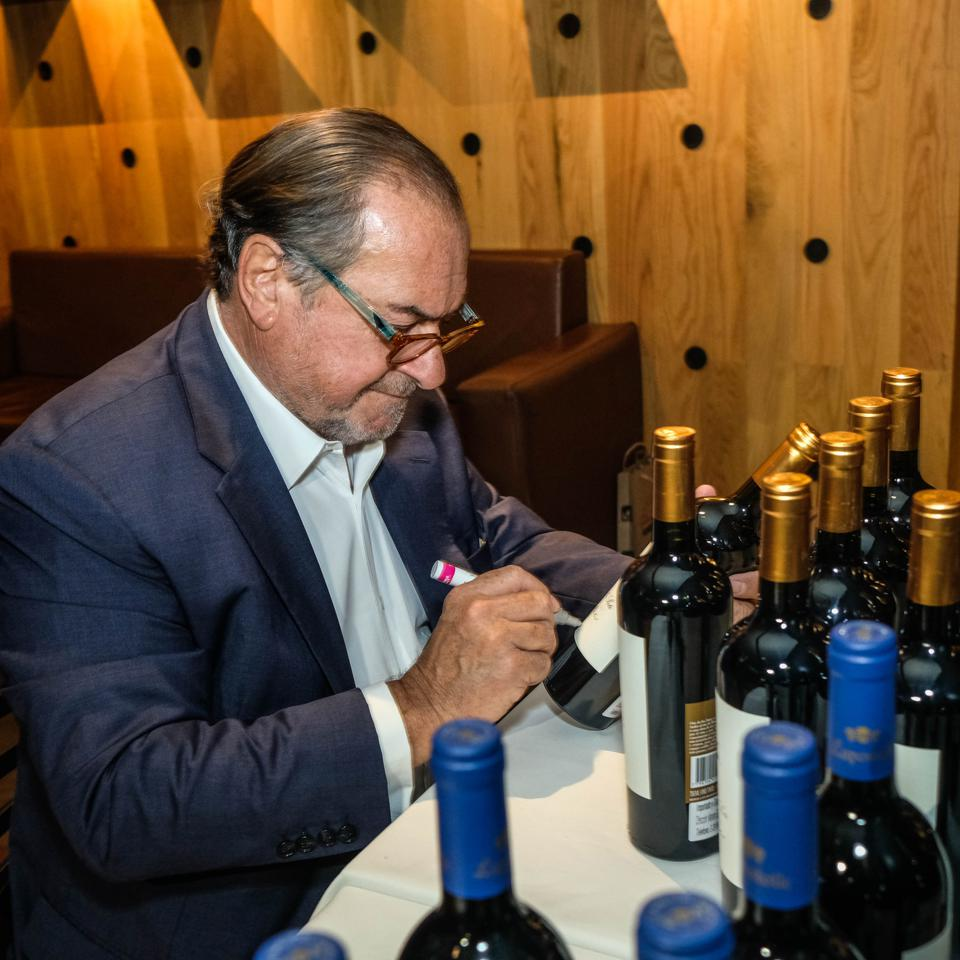 Michel Rolland makes notes on a bottle of wine.
