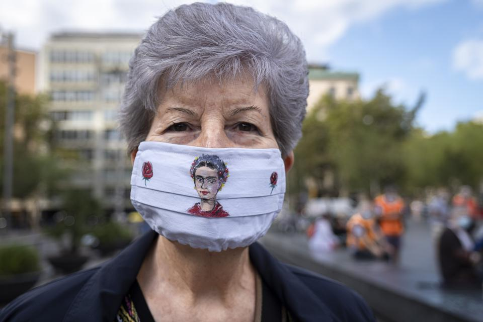 A protester looks on while wearing a face mask as a...