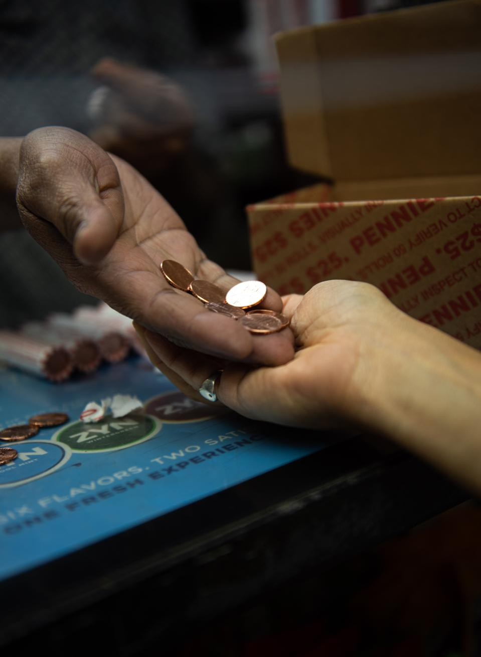 Hands exchanging pennies at a bodega