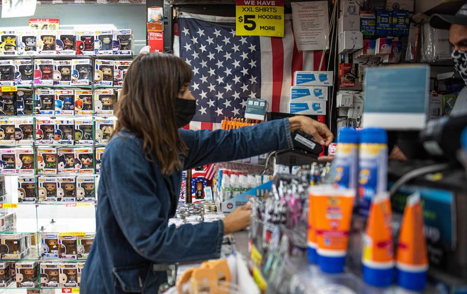 A woman buying something at a bodega in NYC
