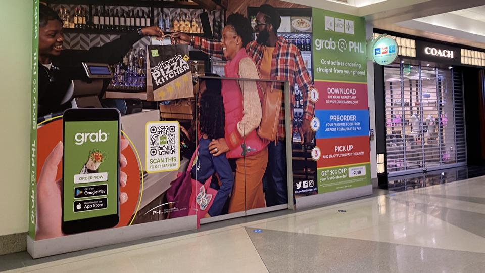 Grab ad covers a closed storefront next to luxury brand Coach phat Philadelphia Airport.