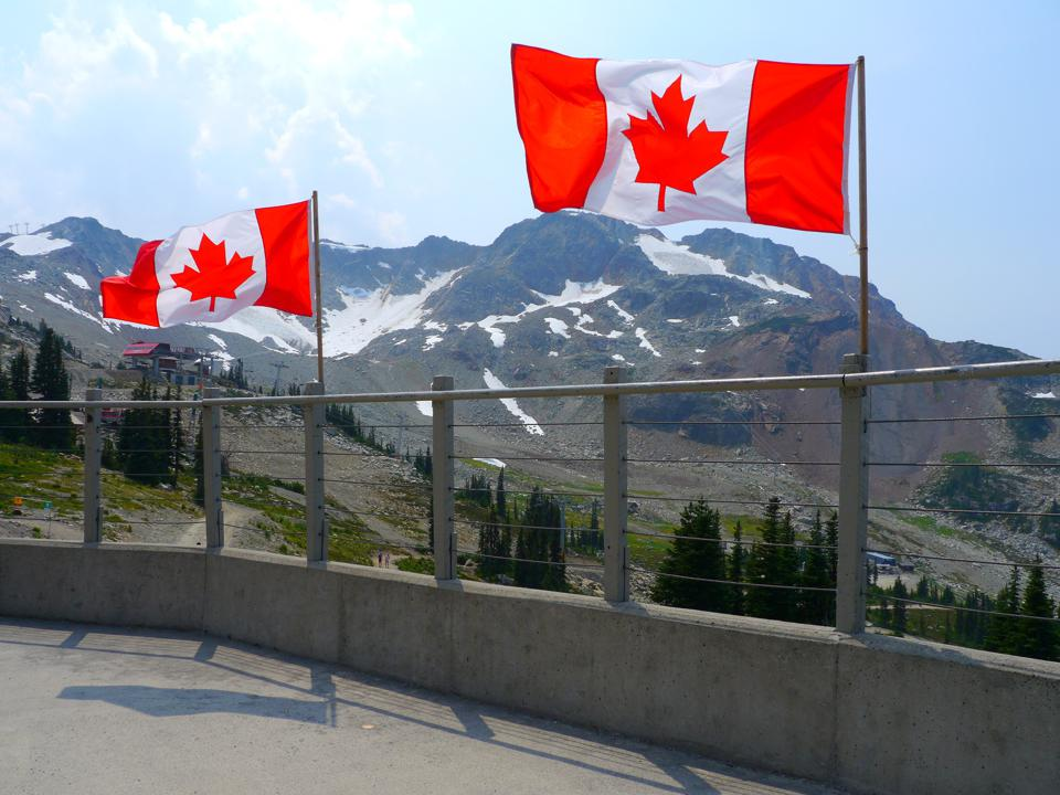 Two Canadian flags flying in the wind, in the background is a mountain with some snow