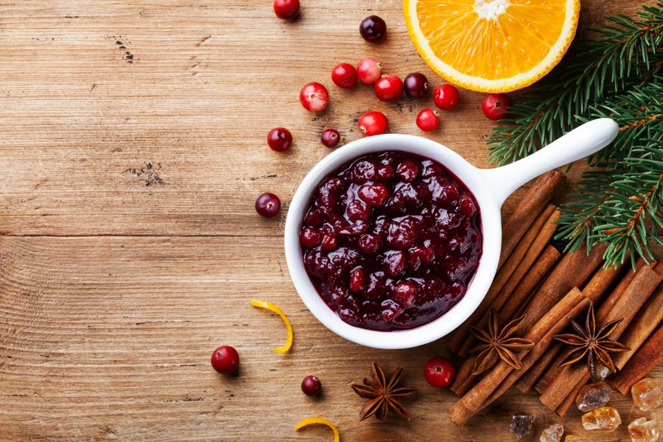 Cranberry sauce in ceramic saucepan with ingredients for cooking decorated with fir tree for Christmas or Thanksgiving day on rustic kitchen table. Top view.