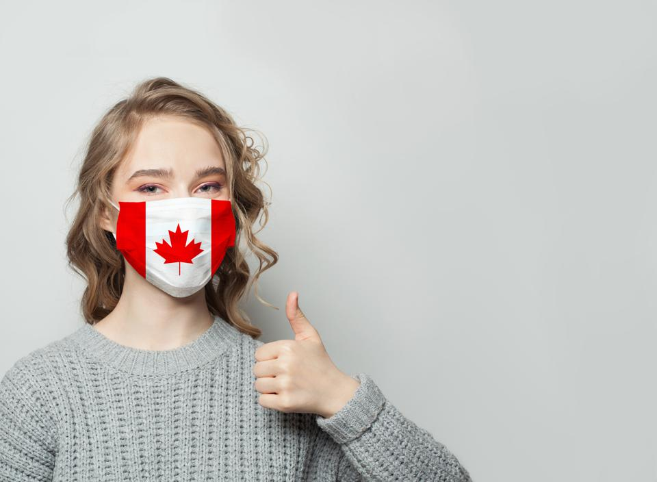 Happy woman in face mask holding thumb up with national flag Canada background. Flu epidemic and virus protection concept